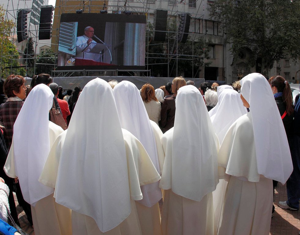 . Nuns watch the newly elected Pope Francis on a giant screen blessing the faithful gathered at St. Peter\'s Square during his Sunday Angelus prayer, at the Plaza de Mayo square in Buenos Aires March 17, 2013. REUTERS/Enrique Marcarian