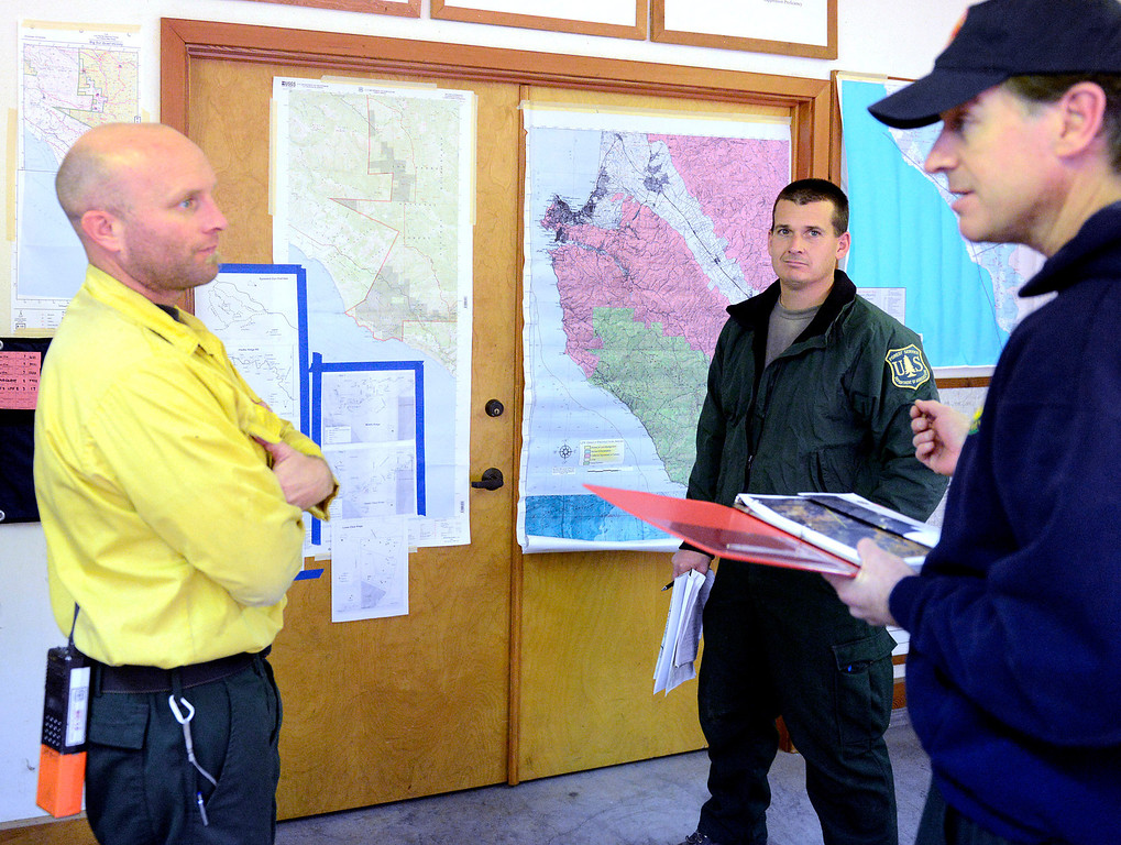 . U.S. Fire Service assistant fire manager Curtis Schwarm, left, and U.S. Fire Service fire manager Pete Harris listen to a briefing from California State Parks Environmental Scientist Jeff Frey in the command center as firefighters battle a wildland fire in the Pfeiffer Ridge area in Big Sur on Monday December 16, 2013. (Photo David Royal/ Monterey County Herald)