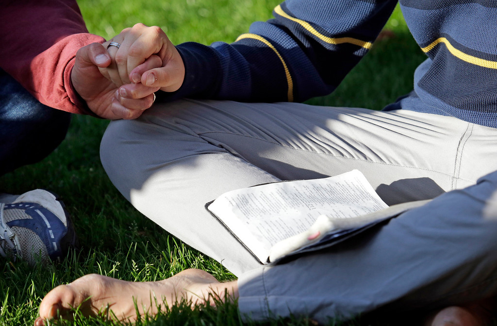 . A Seattle Pacific University student sits with a Bible in his lap in a prayer circle after a church service was full following a shooting on the campus of the university Thursday, June 5, 2014, in Seattle. A lone gunman armed with a shotgun and a knife opened fire in a building on the campus, killing one person before he was subdued with pepper spray by a student as he tried to reload, police said. (AP Photo/Elaine Thompson)