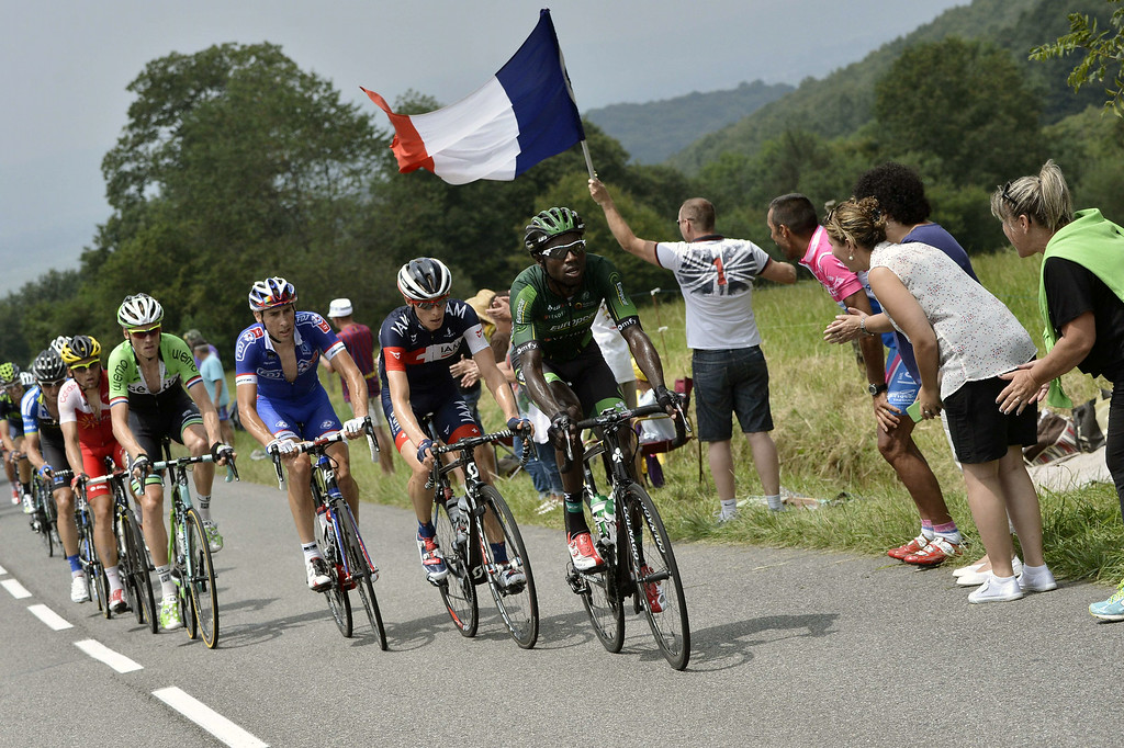 . (From R) France\'s Kevin Reza, Switzerland\'s Marcel Wyss, France\'s Matthieu Ladagnous and Netherland\'s Lars Boom lead a breakaway riding past a supporter holding a French national flag during the 145.5 km eighteenth stage of the 101st edition of the Tour de France cycling race on July 24, 2014 between Pau and Hautacam, southwestern France.  AFP PHOTO / JEFF  PACHOUD/AFP/Getty Images