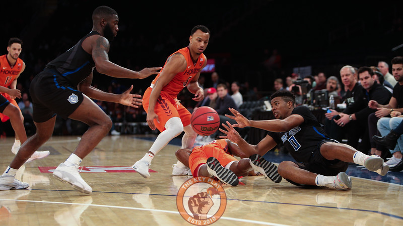 Virginia Tech and St. Louis players lunge for a loose ball during play in Madison Square Garde, Nov. 16, 2017. St. Louis upset Virginia Tech with a 77-71 win.