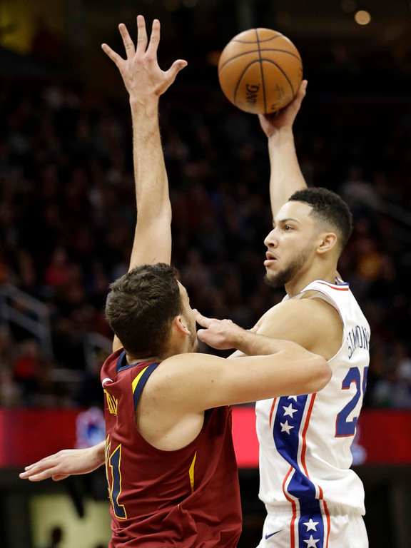 . Philadelphia 76ers\' Ben Simmons, right, shoots over Cleveland Cavaliers\' Ante Zizic during the first half of an NBA basketball game Saturday, Dec. 9, 2017, in Cleveland. (AP Photo/Tony Dejak)
