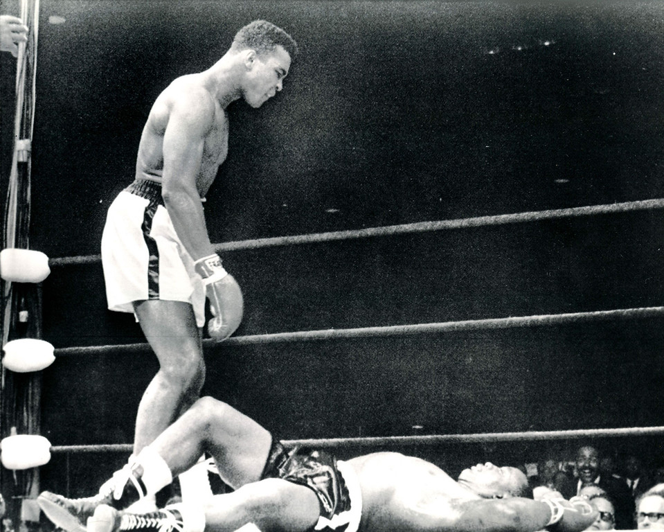 """. JUST ABOUT OVER-The heavyweight champion, one Cassius Clay, glowers at challenger Sonny Liston who lies stretched out on canvas in first and only round of a title bout.  Clay won on a KO.   Liston is stretched out on the deck after taking a right-hand punch from Clay.  The knockout at one minute of the first round was the shortest ever recorded in a heavy-weight championship fight.  The crowd in the Lewiston, Maine arena screamed \""""fake, fake, fake\"""" when it was announced the former champ had been kayoed. 1965  Credit: AP"""