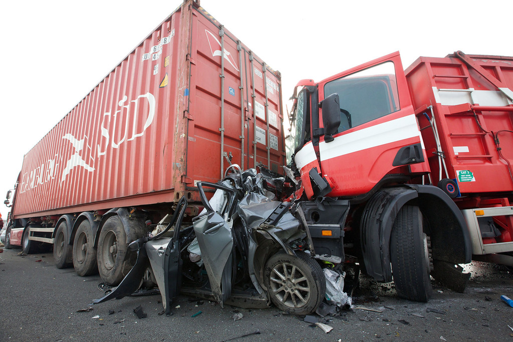 . A car is seen crushed between two trucks during a pileup on a main motorway in Zonnebeke, Belgium on Tuesday, Dec. 3, 2013. (AP Photo/Kurt Desplenter)