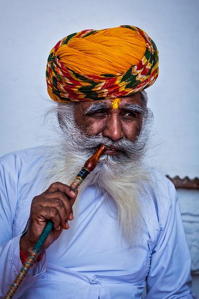 Old Indian man smokes hookah (waterpipe) in Mehrangarh fort