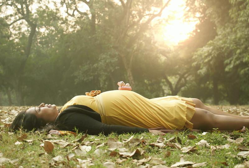 indian-pregnant-women-lying-on-grass.jpg