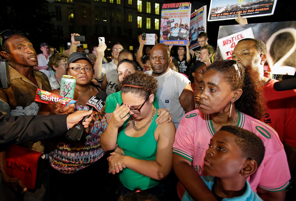 . Demonstrators outside the Seminole County Courthouse react after hearing the verdict of not guilty in the trial of George Zimmerman, Saturday, July 13, 2013, in Sanford, Fla. Zimmerman had been charged with the 2012 shooting death of Trayvon Martin. (AP Photo/John Raoux)