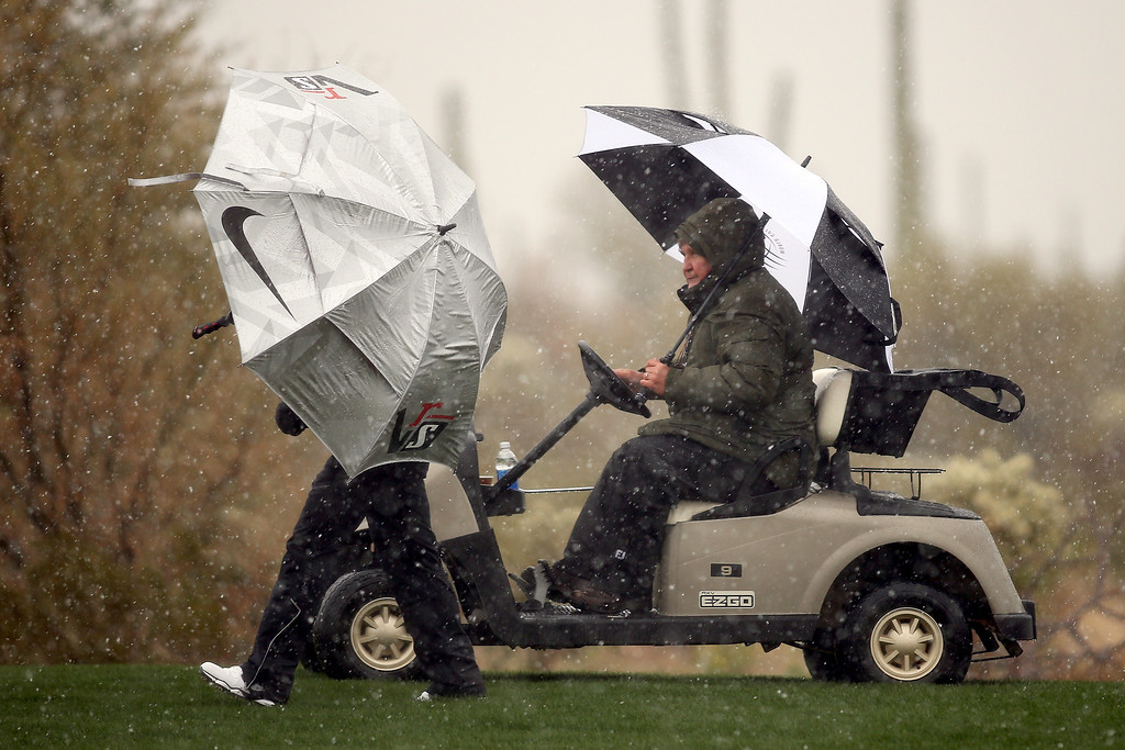 . MARANA, AZ - FEBRUARY 20:  Mark Russell (R), the PGA TOUR\'s Vice President of Rules and Competition talks with Thorbjorn Olesen of Denmark as Olesen stands under an umbrella to avoid the snow and rain, play was suspended due to weather, during the first round of the World Golf Championships - Accenture Match Play at the Golf Club at Dove Mountain on February 20, 2013 in Marana, Arizona.  (Photo by Darren Carroll/Getty Images)