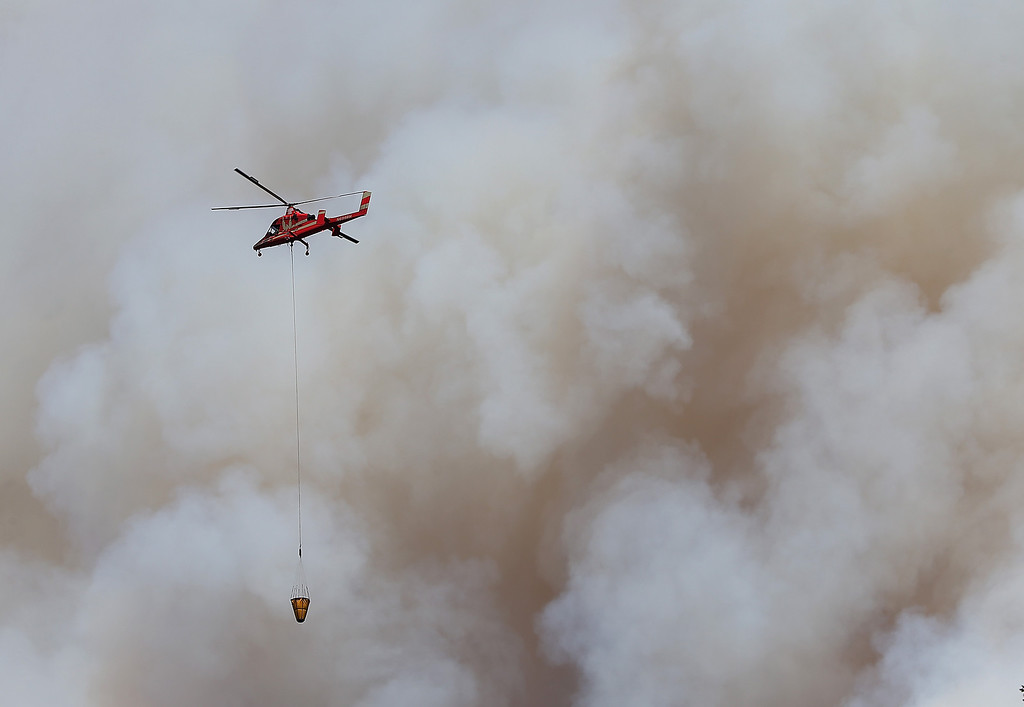 . GROVELAND, CA - AUGUST 22:  A firefighting helicopter flies in front of a plume of smoke from the Rim Fire on August 22, 2013 in Groveland, California. The Rim Fire continues to burn out of control and threatens 2,500 homes outside of Yosemite National Park. Over 1,000 firefighters are battling the blaze that was reduced to only 2 percent containment after it nearly tripled in size overnight.  (Photo by Justin Sullivan/Getty Images)