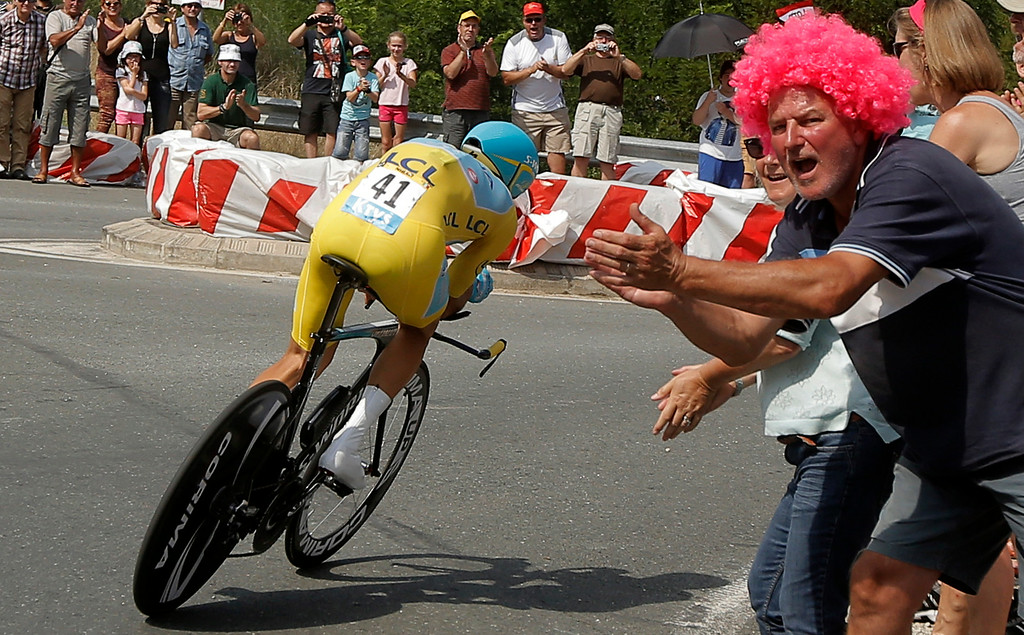 . Spectators cheer as Italy\'s Vincenzo Nibali, wearing the overall leader\'s yellow jersey, steers into a corner the twentieth stage of the Tour de France cycling race, an individual time-trial over 54 kilometers (33.6 miles) with start in Bergerac and finish in Perigueux, France, Saturday, July 26, 2014. (AP Photo/Laurent Cipriani)