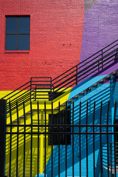 Metal fence by colorful building, Minneapolis, Hennepin County, Minnesota, USA