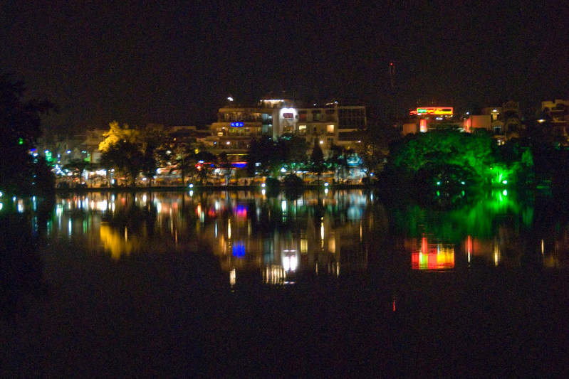 Bright city lights reflecting in lake at night - Hanoi, Vietnam