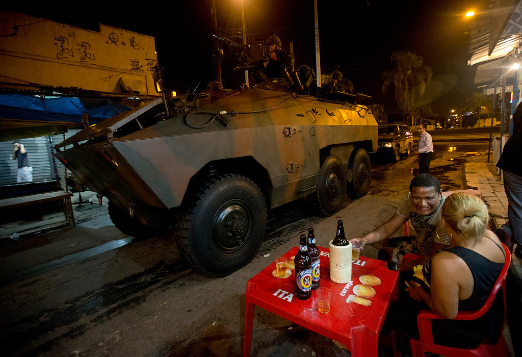 . A couple drink beer while Army soldiers enter  to occupy the Mare slum complex in Rio de Janeiro, Brazil, Saturday, April 5, 2014. More than 2,000 Brazilian Army soldiers moved into the Mare slum complex early Saturday in a bid to improve security and drive out the heavily armed drug gangs that have ruled the sprawling slum for decades. (AP Photo/Silvia Izquierdo)