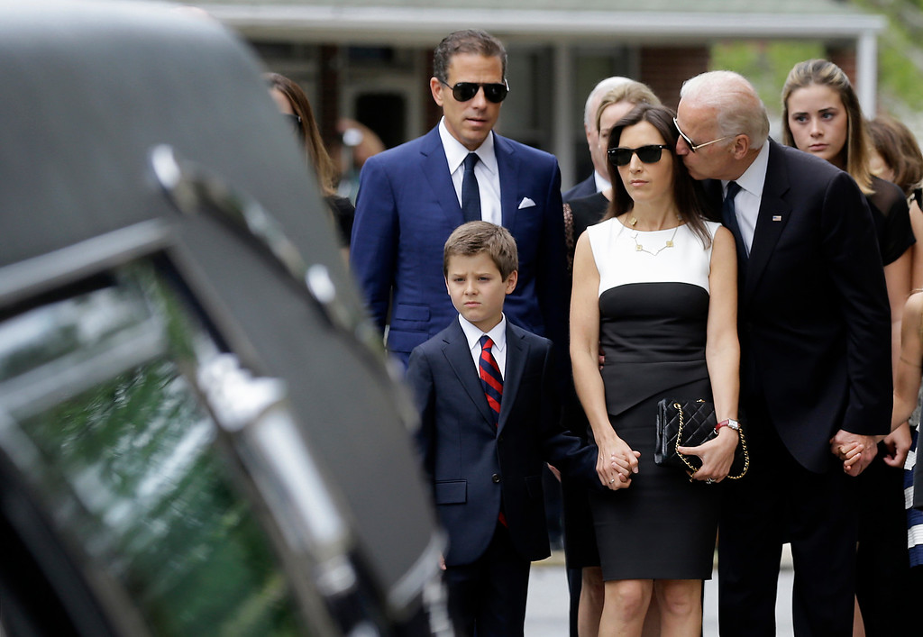 . Vice President Joe Biden kisses Hallie Biden, the widow of the vice president\'s son, former Delaware Attorney General Beau Biden, before his funeral services, Saturday, June 6, 2015, at St. Anthony of Padua Roman Catholic Church in Wilmington, Del. Also pictured is Beau Biden\'s son, Hunter, bottom left, and brother Hunter. Beau Biden died of brain cancer May 30 at age 46. (AP Photo/Patrick Semansky)