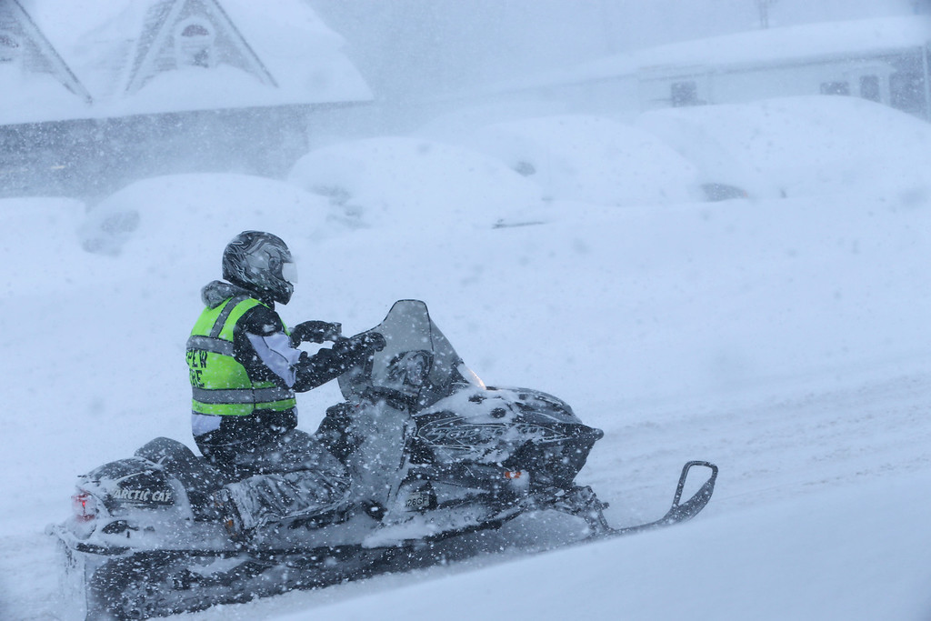 . A Depew firefighter uses a snowmobile to travel down Transit Road, Tuesday, Nov. 18, 2014. Several feet of lake-effect snow paralyzed the Buffalo area Tuesday, forcing state troopers to deliver blankets and other supplies to motorists stranded on the New York State Thruway and adding an ominous note to a wintry season that\'s already snarling travel and numbing fingers from the Midwest to the Carolinas.  (AP Photo/The Buffalo News, Derek Gee)
