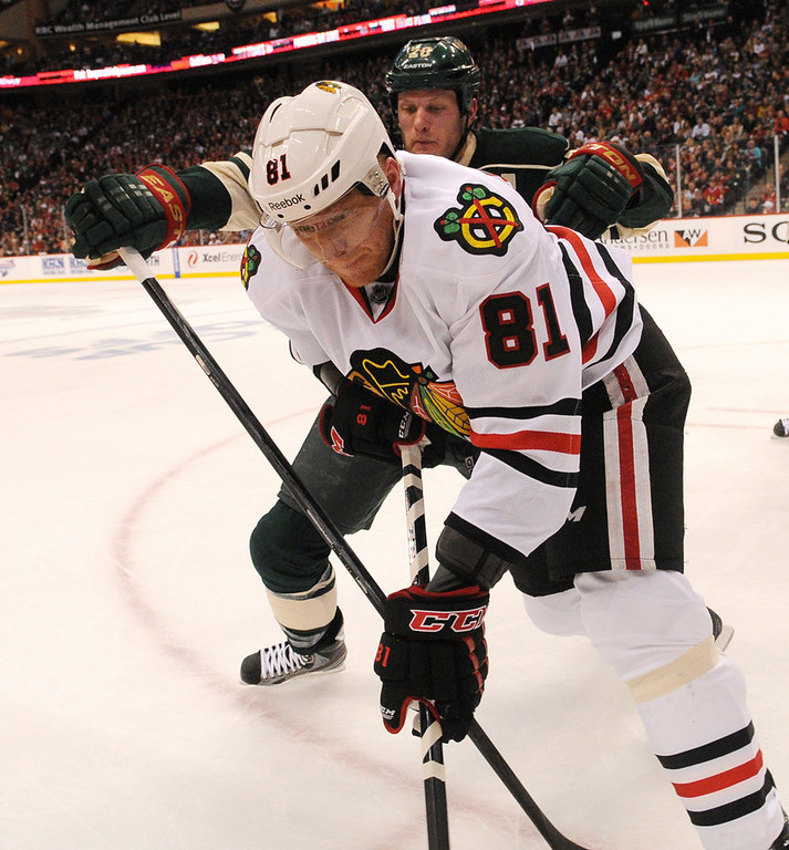 . Minnesota defenseman Ryan Suter, rear, fights for the puck with Chicago right wing Marian Hossa against the boards in the second period. (Pioneer Press: John Autey)