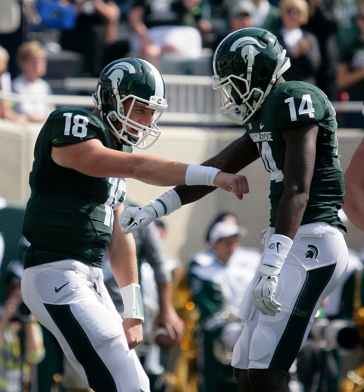 . Michigan State quarterback Connor Cook (18) and receiver Tony Lippett (14) celebrate Lippett\'s touchdown reception against Eastern Michigan during the first quarter of an NCAA college football game, Saturday, Sept. 20, 2014, in East Lansing, Mich. (AP Photo/Al Goldis)