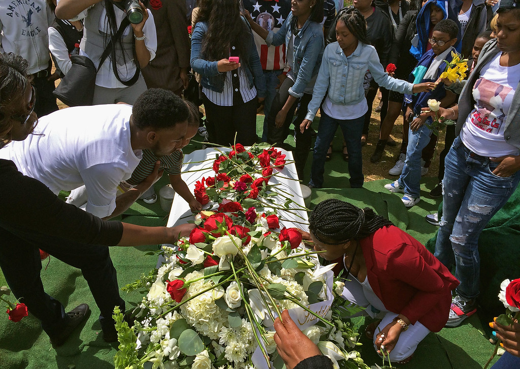 . BALTIMORE, MD - APRIL 27:  Friends and relatives lay flowers on and kiss Freddie Gray\'s casket before it is lowered into the ground at the Woodland Cemetery April 27, 2015 in Baltimore, Maryland. Gray, 25, was arrested for possessing a switch blade knife April 12 outside the Gilmor Homes housing project on Baltimore\'s west side. According to his attorney, Gray died a week later in the hospital from a severe spinal cord injury he received while in police custody.  (Photo by Chip Somodevilla/Getty Images)