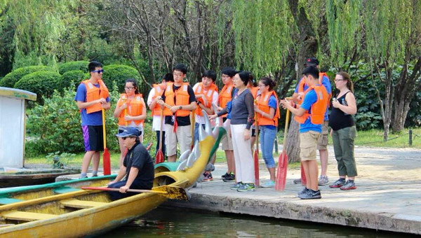 Concordia International School Shanghai students and chaperones watch a rowing demonstration. Teams were told to row more vertically, perpendicular to the water. The drummer would keep a pace, clacking and pounding to keep the paddlers synchronized.