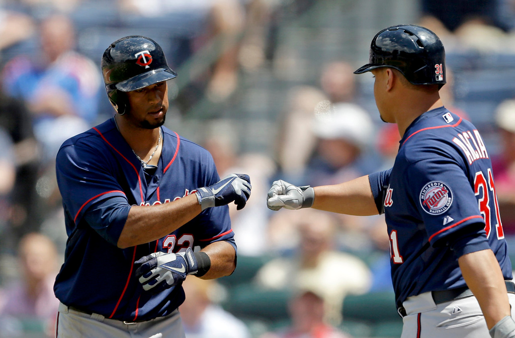 . Minnesota\'s Aaron Hicks, left, fist-bumps teammate Oswaldo Arcia after Hicks hit a solo home run in the ninth inning against the Braves. (AP Photo/David Goldman)
