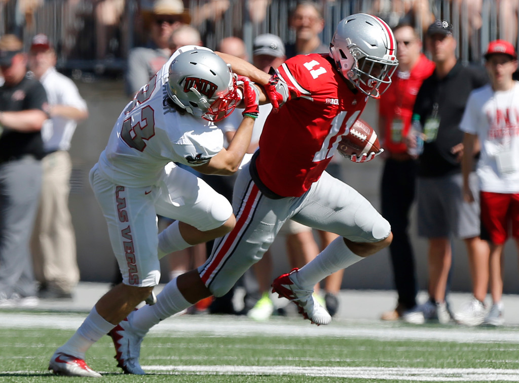 . Ohio State receiver Austin Mack, right, stiff arms UNLV defensive back Dalton Baker during the first half of an NCAA college football game Saturday, Sept. 23, 2017, in Columbus, Ohio. (AP Photo/Jay LaPrete)