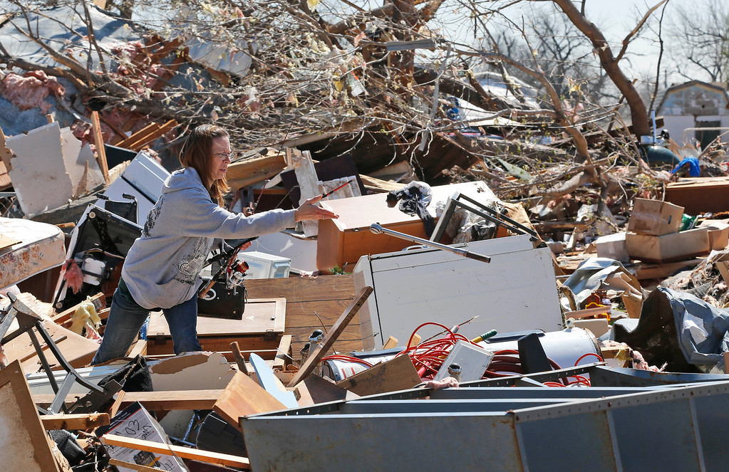 . Brenda English sorts through some of her belongings at her tornado-destroyed mobile home in Sand Springs, Okla.,, Thursday, March 26, 2015. (AP Photo/Sue Ogrocki)