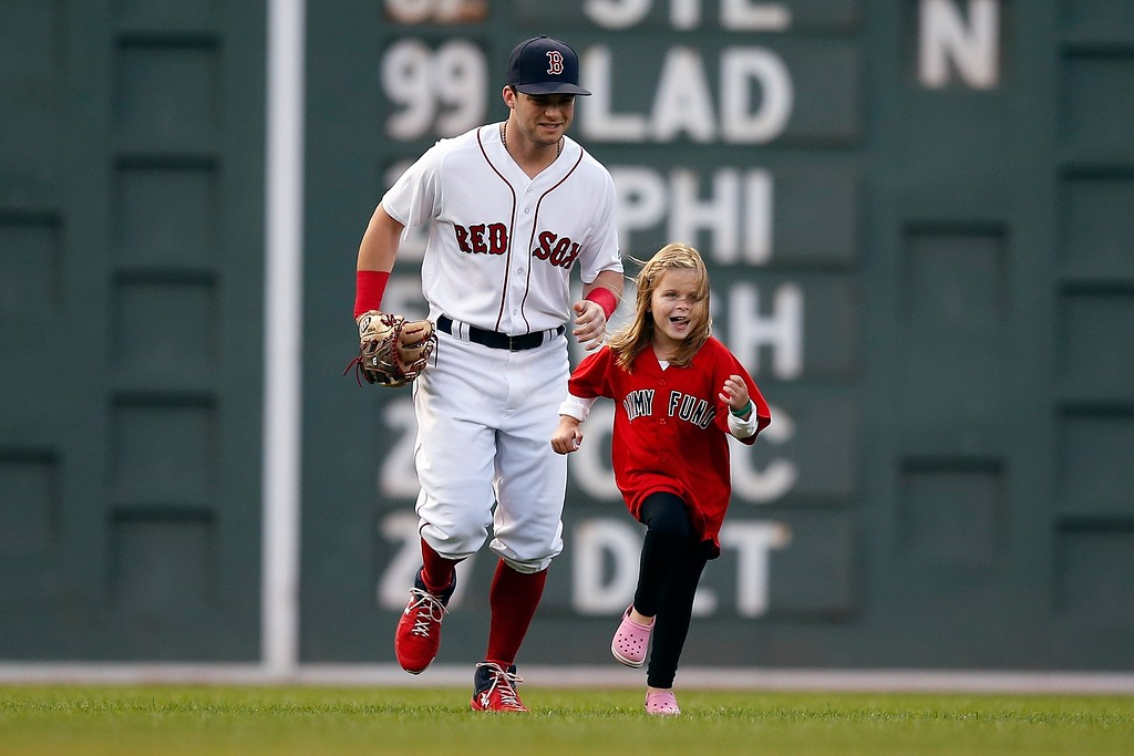 . A young cancer patient runs on the field with Boston Red Sox\'s Andrew Benintendi before a baseball game against the Cleveland Indians in Boston, Tuesday, Aug. 21, 2018. (AP Photo/Michael Dwyer)
