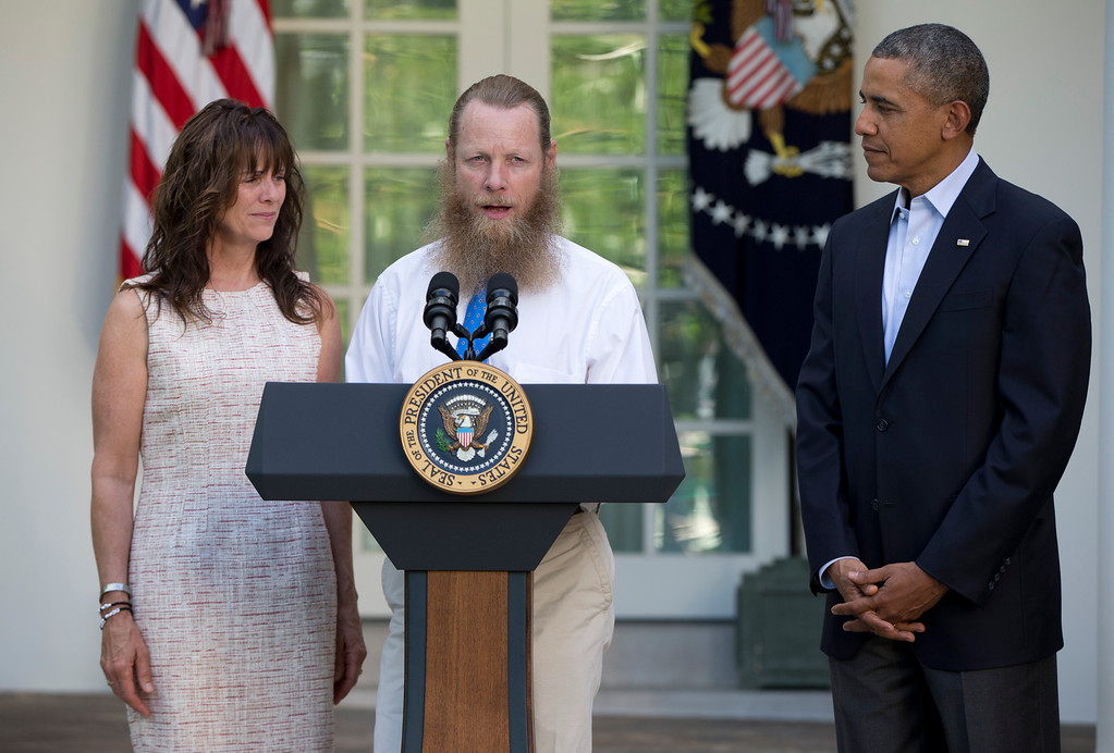 . President Barack Obama looks to Jani Bergdahl and Bob Bergdahl, the parents of U.S. Army Sgt. Bowe Bergdahl, in the Rose Garden of the White House in Washington, Saturday, May 31, 2014, as Bob Bergdahl speaks about the release of their son. Bergdahl, 28, had been held prisoner by the Taliban since June 30, 2009. He was handed over to U.S. special forces by the Taliban in exchange for the release of five Afghan detainees held by the United States. (AP Photo/Carolyn Kaster)