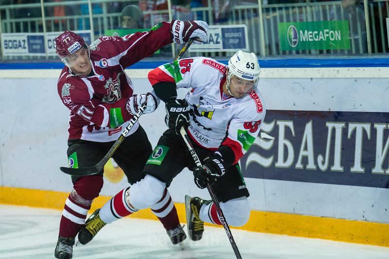 Marcel Hascak (77) izdara spēka pa\n\emienu pret Traktor Chelyabinsk hokejistu Kondratyev Maxim (63)
