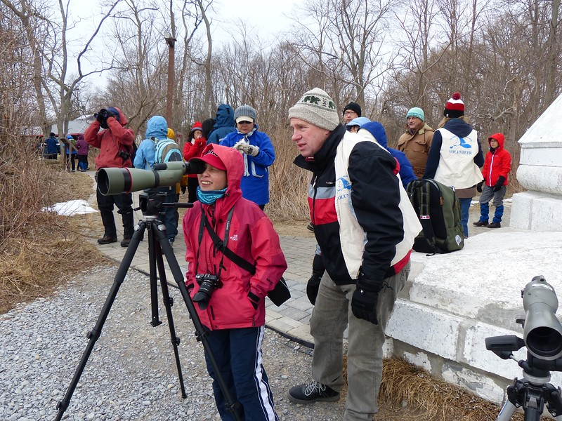 Bruce Parker assists a Park visitor with using the spotting scope to view some ducks.