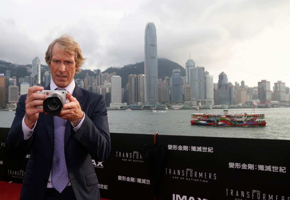 ". American director Michael Bay plays with a camera on the red carpet as he arrives for the world premiere of the movie ""Transformers 4: Age of Extinction\"" in Hong Kong Thursday, June 19, 2014. The latest installment in the blockbuster series of \""Transformers\"" films is making its world premier not in the usual entertainment hubs of Los Angeles or New York but in the wealthy Chinese metropolis of Hong Kong, the latest sign of Hollywood\'s increasing focus on China\'s booming film market. (AP Photo/Kin Cheung)"