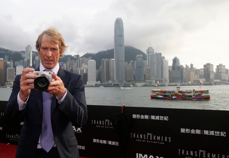 """. American director Michael Bay plays with a camera on the red carpet as he arrives for the world premiere of the movie \""""Transformers 4: Age of Extinction\"""" in Hong Kong Thursday, June 19, 2014. The latest installment in the blockbuster series of \""""Transformers\"""" films is making its world premier not in the usual entertainment hubs of Los Angeles or New York but in the wealthy Chinese metropolis of Hong Kong, the latest sign of Hollywood\'s increasing focus on China\'s booming film market. (AP Photo/Kin Cheung)"""