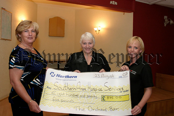 "Eileen Sands (left) and Geneviveve Mc Gahan (right) present a cheque for £875.00 to Mairin Sands (hospice), The money was raised at a ""Night of the races"" in the Orchard Bar, 07W35N55"