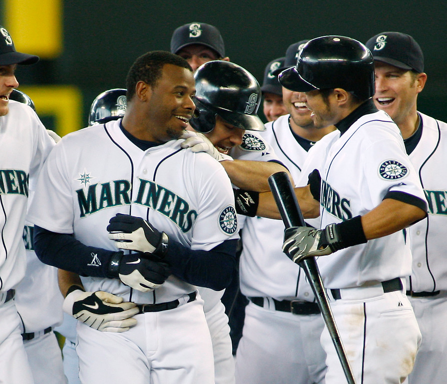 . Seattle Mariners\' Ken Griffey Jr., left, is mobbed by teammates including Ichiro Suzuki, right, after Griffey hit the  game-winning, RBI pinch-hit single in the ninth inning a baseball game against the Toronto Blue Jays, Thursday, May 20, 2010, in Seattle. Milton Bradley scored on the hit, which gave the Mariners a 4-3 win. (AP Photo/Ted S. Warren)