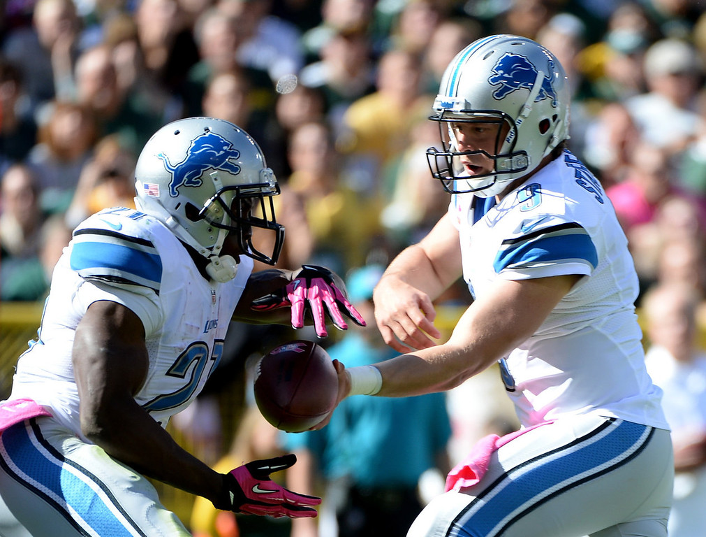 . Matthew Stafford #9 of the Detroit Lions hands off to Reggie Bush #21 during the second quarter against the Green Bay Packers at Lambeau Field on October 6, 2013 in Green Bay, Wisconsin.  (Photo by Harry How/Getty Images)