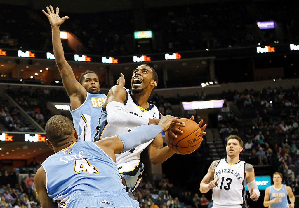 . Memphis Grizzlies guard Mike Conley (11) gets fouled on his way to the basket against Denver Nuggets guards Randy Foye (4) and Aaron Brooks, back, in the second half of an NBA basketball game Friday, April 4, 2014, in Memphis, Tenn. The Grizzlies won 100-92. (AP Photo/Lance Murphey)