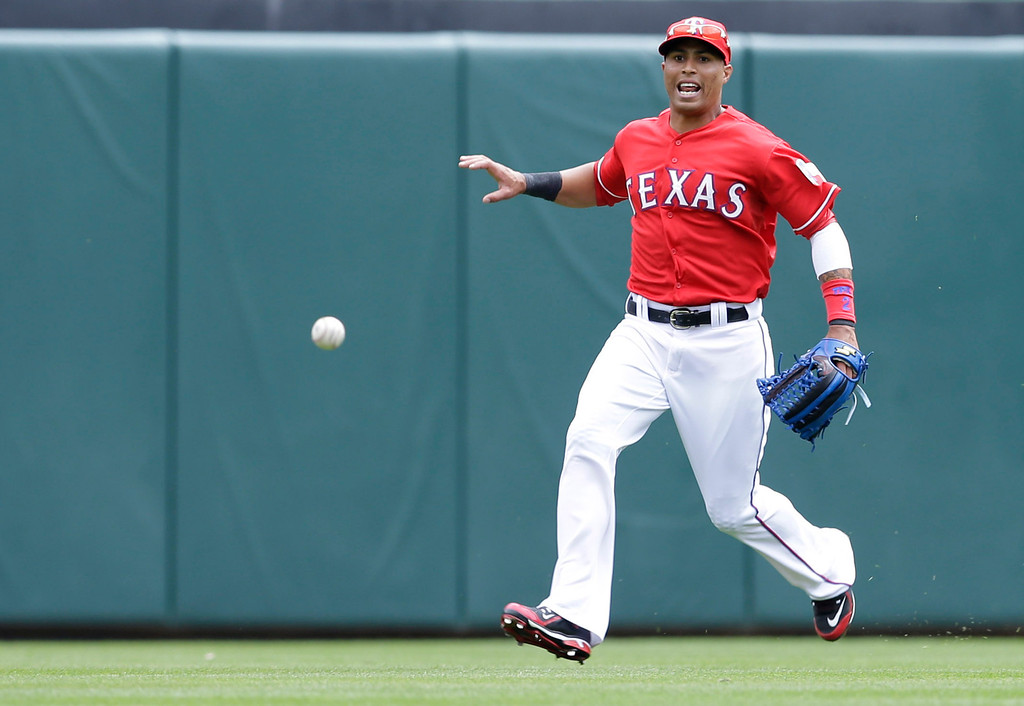. Texas Rangers center fielder Leonys Martin fields the ball against the Philadelphia Phillies during the third inning of an opening day baseball game at Globe Life Park, Monday, March 31, 2014, in Arlington, Texas.  (AP Photo/Tony Gutierrez)