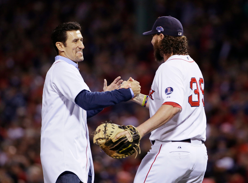 . Boston Red Sox catcher Jarrod Saltalamacchia (39) shakes hands with former Red Sox shortstop Nomar Garciaparra, left, after Garciaparra tossed the ceremonial first pitch before Game 1 of the American League baseball championship series against the Detroit Tigers Saturday, Oct. 12, 2013, in Boston. (AP Photo/Matt Slocum)