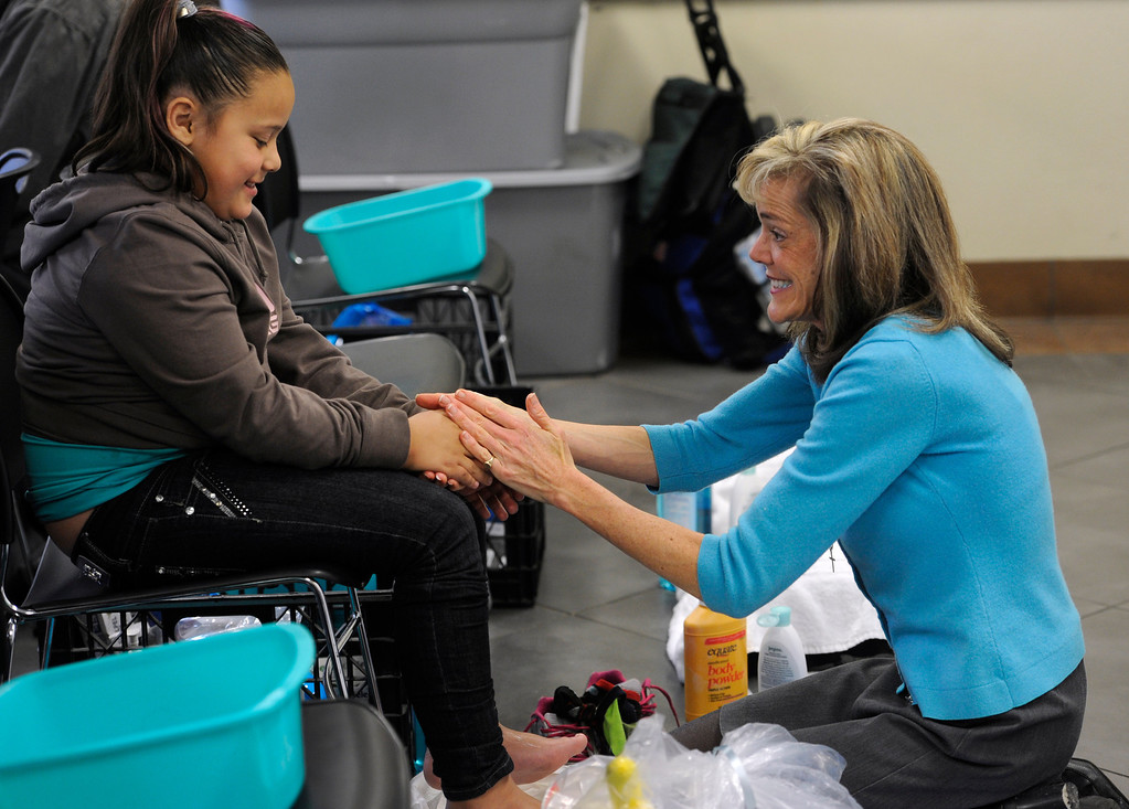 . DEVNER, CO.- MARCH 29: After washing her feet, volunteer Sarah Waite, right, moisturizes seven-year-old Dayanara Oropeza\'s feet and hands. The Denver Rescue Mission partners with Volunteers of American and Runner\'s Roost to supply approximately 600 homeless adults and children with a new pair of shoes, sock and an Easter meal at the 20th Annual Easter Celebration  at the Rescue Mission on Lawrence Street. Many of the homeless had their feet washed by volunteers, symbolic of the part of the Christian tradition, mirroring Jesus\' washing of his disciples\' feet.(Photo By Kathryn Scott Osler/The Denver Post)