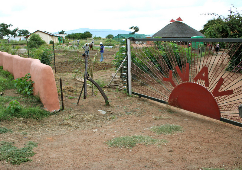 "the entrance to the project site.  ""youth with a vision"" (YWAV) is NextAid's partner organization.  NextAid has raised money and managed the construction of this site in dennilton, south africa.  the site is set to be an ""eco-village"" for aids orphans.  the orphanage will be run by YWAV.  the YWAV site is NextAid's pilot project."