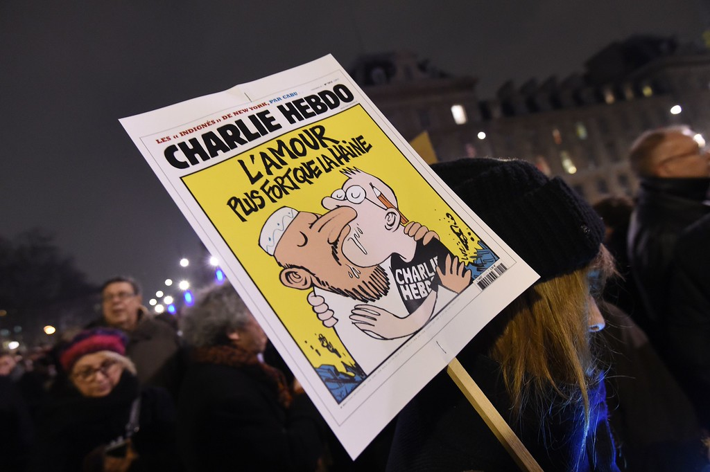 ". A woman holds a Charlie Hebdo\'s front page reading ""Love stronger than hate\"" during a gathering at the Place de la Republique (Republic square) in Paris, on January 7, 2015, following an attack by unknown gunmen on the offices of the satirical weekly, Charlie Hebdo. France\'s Muslim leadership sharply condemned the shooting at the Paris satirical weekly that left at least 12 people dead as a \""barbaric\"" attack and an assault on press freedom and democracy. AFP PHOTO / DOMINIQUE  FAGET/AFP/Getty Images"