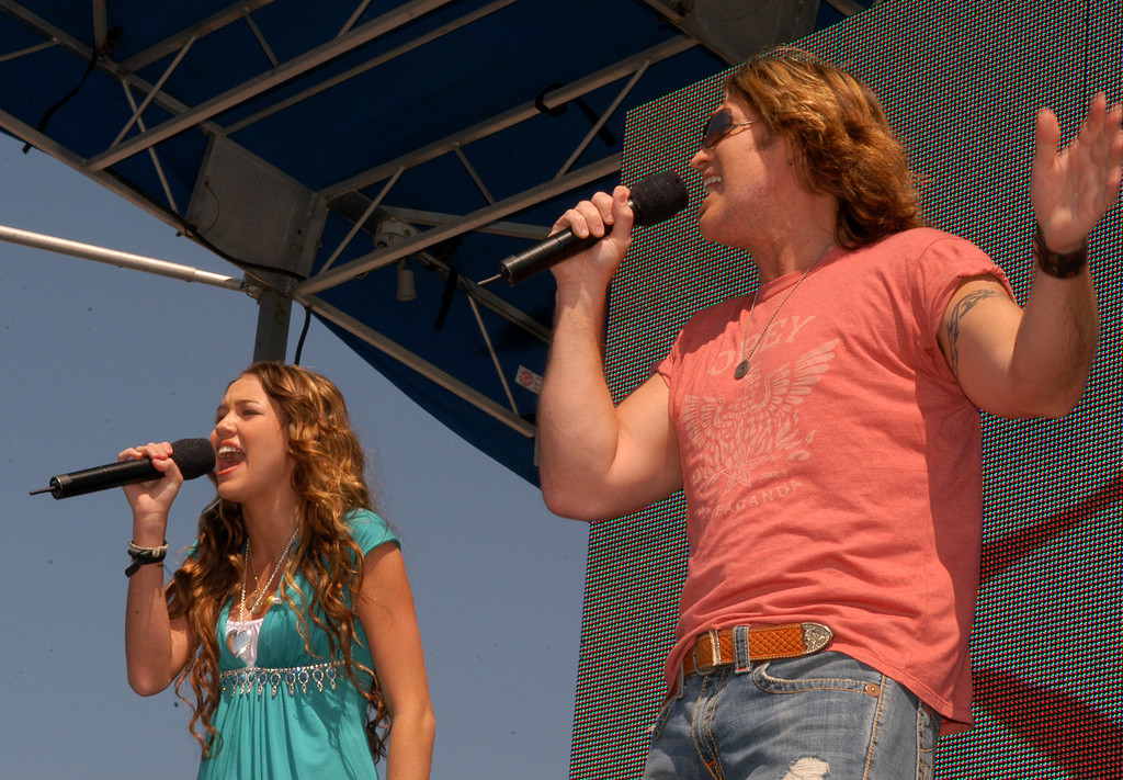 """. Actor, singer Billy Ray Cyrus performs with his daughter Miley Cyrus on the pier in Santa Monica, Calif., Saturday, Sept. 16, 2006, during the Boys and Girls Clubs Day for Kids.  The pair star together in the television show \""""Hannah Montana.\""""  The Boys and Girls Clubs of America held the event to celebrate value of spending meaningful time with family.  (AP Photo/Boys and Girls Clubs of America, John Hayes)"""