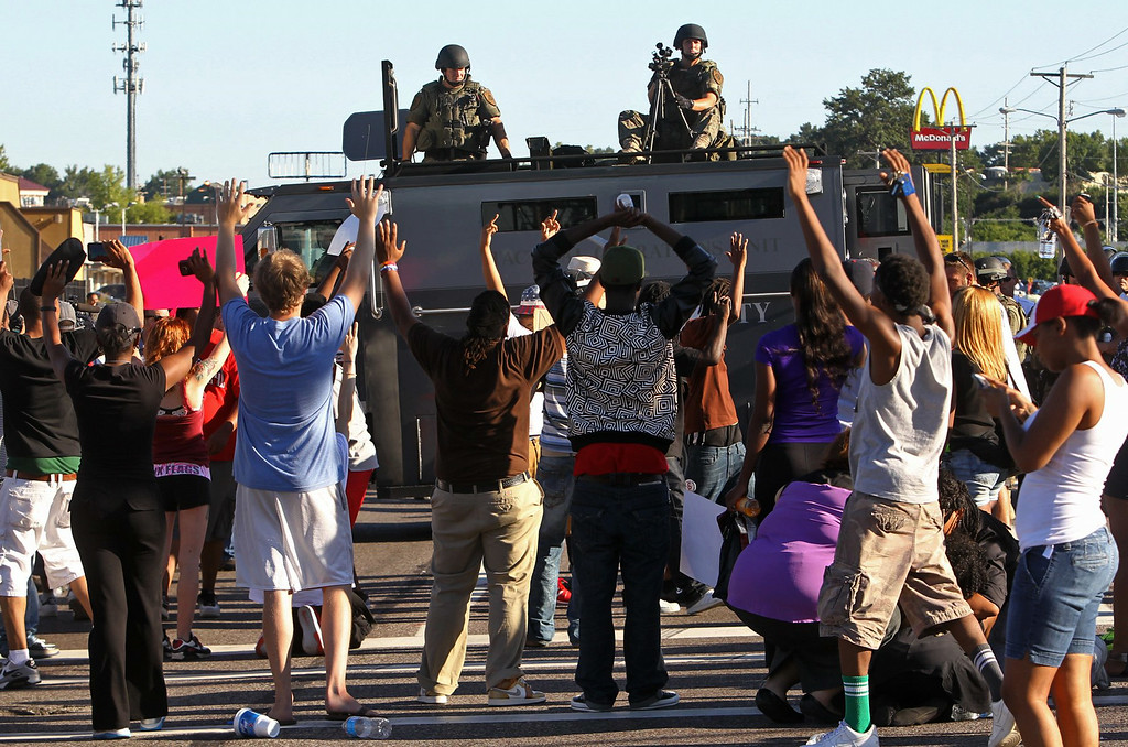 . Protesters raise their hands in front of police atop an armored vehicle in Ferguson, Mo. on Wednesday, Aug. 13, 2014. On Saturday, Aug. 9, 2014, a police officer fatally shot Michael Brown, an unarmed black teenager, in the St. Louis suburb. (AP Photo/St. Louis Post-Dispatch, J.B. Forbes)