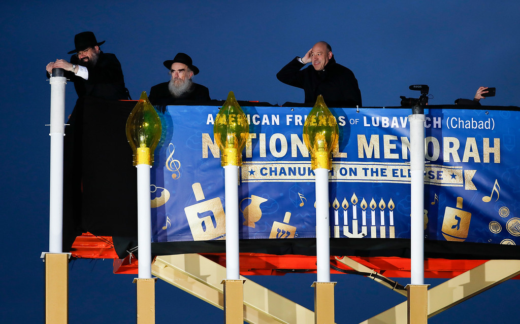 . From left, Rabbi Levi Shemtov, with Rabbi Abraham Shemtov and National Economic Director Gary Cohn, struggles in the wind to light the Menorah during the annual National Menorah Lighting, in celebration of Hanukkah, on the Ellipse near the White House in Washington, Tuesday, Dec. 12, 2017. (AP Photo/Carolyn Kaster)