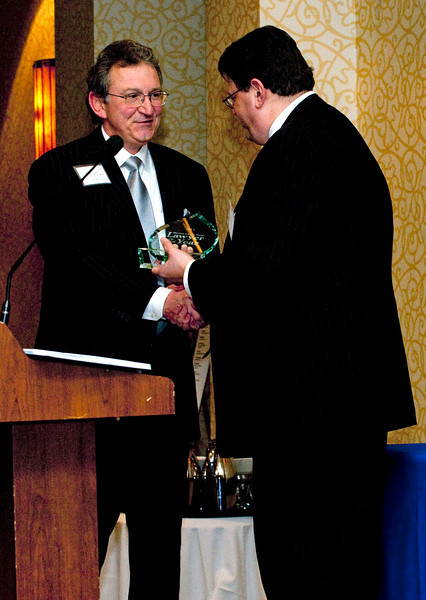 George Sinas accepts the Lawyer of the Year award from Michigan Lawyers Weekly publisher Paul Fletcher in Troy, MI on March 21, 2013.