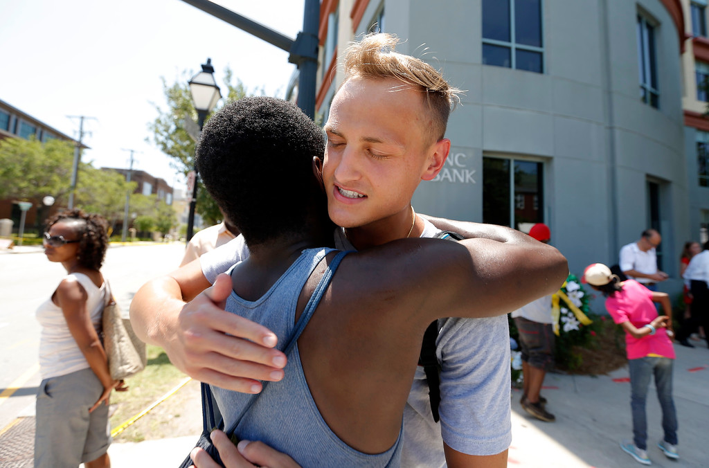 . Tyler Francis, right, hugs Shondrey Dear after praying together, Thursday, June 18, 2015 at a make-shift memorial near the Emanuel AME Church following a shooting Wednesday night in Charleston, S.C. Shooting suspect Dylann Storm Roof, 21, was captured without resistance in North Carolina Thursday after an all-night manhunt, Charleston\'s police chief Greg Mullen said. (AP Photo/Stephen B. Morton)
