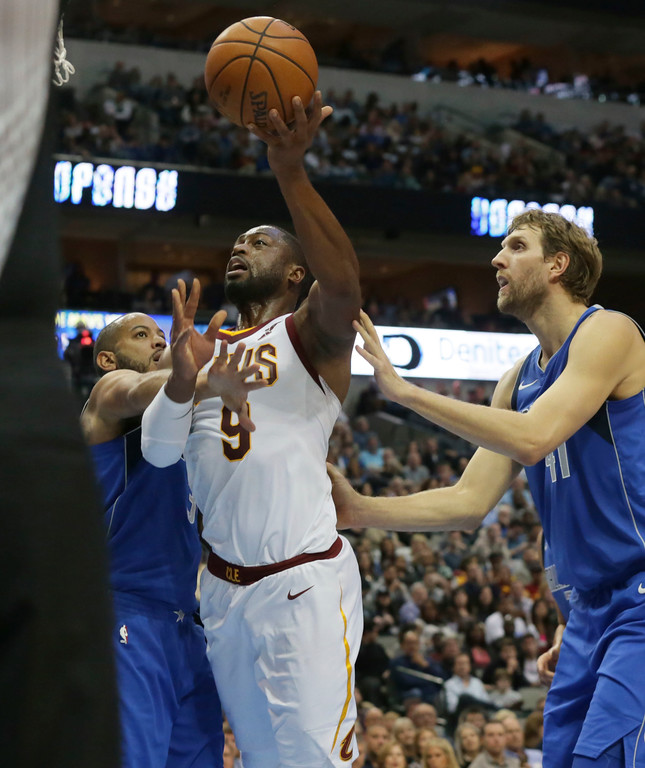 . Cleveland Cavaliers guard Dwyane Wade (9) drives against Dallas Mavericks defenders Devin Harris (34) and Dirk Nowitzki (41) during the first half of an NBA basketball game in Dallas, Saturday, Nov. 11, 2017. (AP Photo/LM Otero)