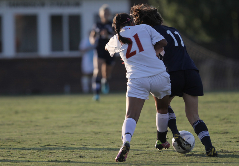 Brianna Fraire (21) fights to get the ball back from Charleston Southern's player