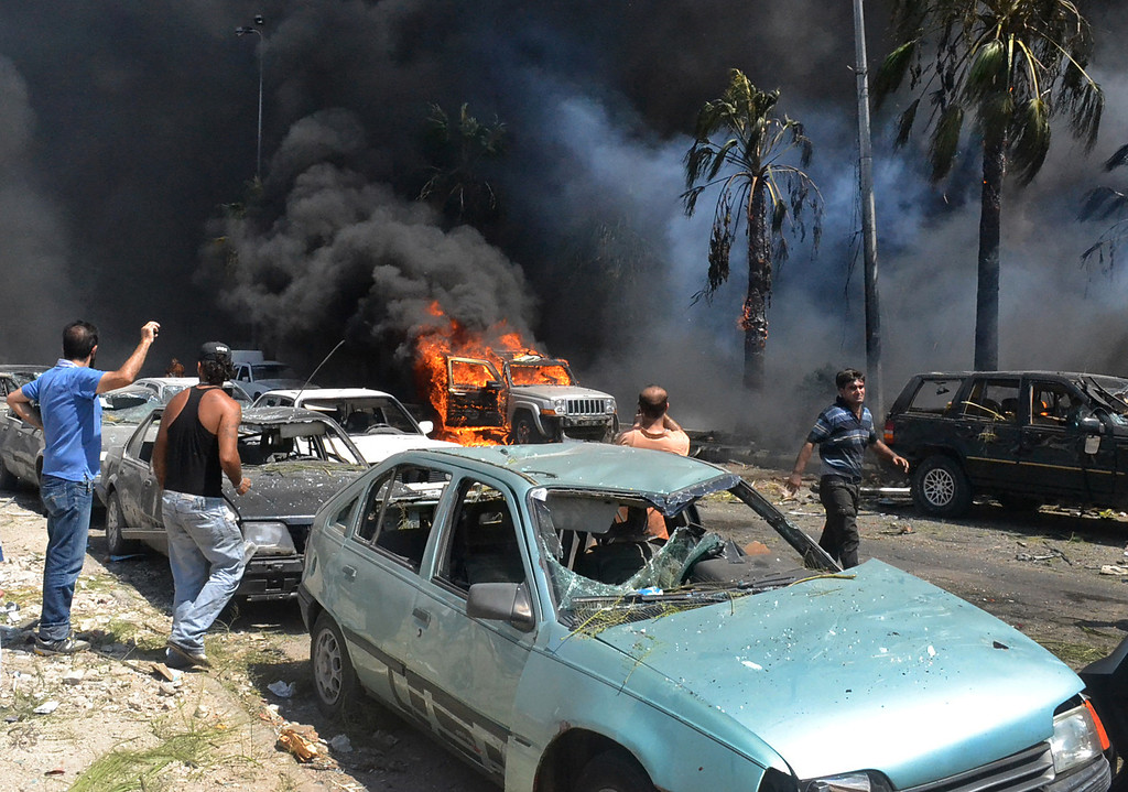 . Lebanese men gather at the site of an explosion outside of a mosque, in the northern city of Tripoli, Lebanon, Friday Aug. 23, 2013.   (AP Photo)