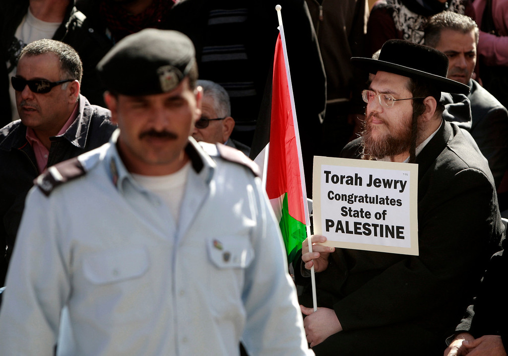 . A Hassidic Jew holds a Palestinian flag and a sign during a rally supporting the Palestinian UN bid for observer state status, in the West bank city of Ramallah, Thursday, Nov. 29, 2012. The Palestinians are certain to win U.N. recognition as a state on Thursday but success could exact a high price: delaying an independent state of Palestine because of Israel\'s vehement opposition. (AP Photo/Majdi Mohammed)